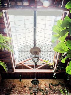 A Venetian hanging lantern (one of a pair) is wired for electricity and hangs from a skylight Van Duysen designed to look like a throwback to a Victorian greenhouse. Exposed copper heating pipes glow in the light on sunny days. Indoor Courtyard, Indoor Greenhouse, Conservatory Roof, Victorian Greenhouses, Rose Uniacke, Terracotta Floor, London Townhouse, Fire Doors, Hanging Lanterns