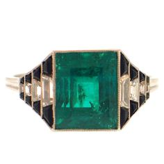 Art Deco Emerald Diamond Onyx Ring  USA  Circa 1920  This beautiful Art Deco ring featuring and emerald-cut emerald weighing approximately 5.00 carats, accented at the sides by diamond and onyx graduated steps.