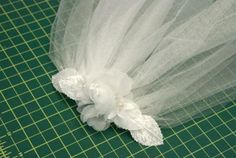 Directions on making a simple bridal veil:  Tulle, comb, satin ribbon, needle, white thread, silk flowers or other embellishments, hot glue gun.  First Communion veil