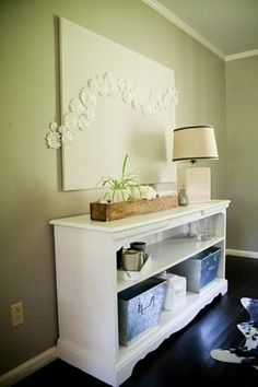 Upcycled dresser = tv stand Like how the doily's run off the framed canvas.