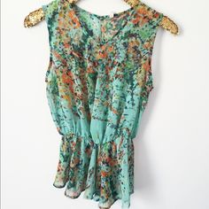 | floral peplum top | Very pretty floral peplum top. Chiffon material. Elastic in the peplum feature. Variety of colors on mint green. There's no size listed but it fits like a small. Small tear in hemline- as seen in pictures. Priced low for that reason. Tops Tank Tops