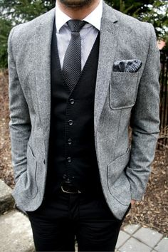 Shop this look for $286:  http://lookastic.com/men/looks/blazer-and-waistcoat-and-tie-and-dress-shirt-and-pocket-square-and-belt-and-dress-pants/749  — Grey Wool Blazer  — Black Waistcoat  — Black and White Polka Dot Tie  — White Vertical Striped Dress Shirt  — Grey Paisley Pocket Square  — Black Leather Belt  — Black Dress Pants