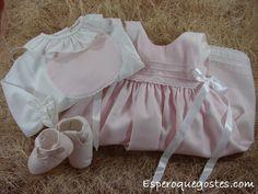 O conjunto é de coeiro cor de rosa, sapatos e babete iguais e camisa branca de folhos.