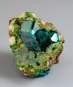 Dioptase on Duftite and Calcite: from the Tsumeb Mine, Otjikoto Region, Tsumeb, Namibia. A grass green matrix of duftite and calcite is host to a 12 mm tall dioptase crystal.