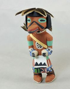 "4 1/2"" tall, carved from dried cottonwood root, painted and decorated with feathers, a cloth kilt and a leather quiver with an arrow."