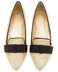 6c03bdd3740 Guldglittrande skor med låga klackar och brett svart band med rosett över  foten.