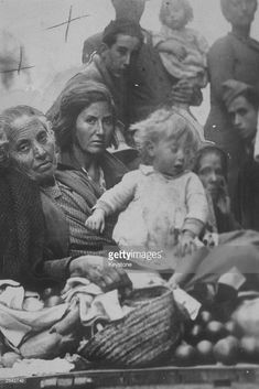 A grandmother, her daughter and granddaughter, refugees from the Spanish Civil war, arriving in Valencia carrying their belongings.