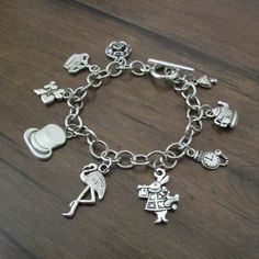 This bracelet is inspired by Alice in Wonderland. It features antique silver mushroom, tea set, pocket watch, White Rabbit, flamingo, mad hatter top hat, card suit, Queen of Hearts crown, and rose charms. Standard adult bracelet size is 7.  To measure for bracelet size: Gently wrap a flexible measuring tape around your wrist, just below the wrist bone or in the same place where you would wear a watch. Take note of the measurement, then add an extra 1/2 to 1 (depending on how much extra room…