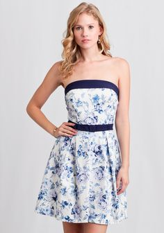 This darling cotton-blend white dress is designed in a strapless silhouette with a floral print in hues of blue and purple.