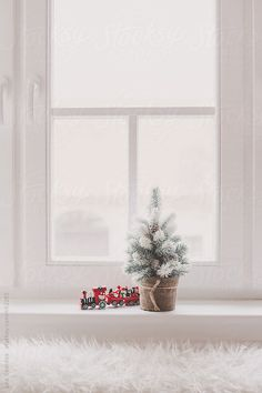Small snow covered christmas tree decoration and a toy train on a window sill by LeaCsontos | Stocksy United