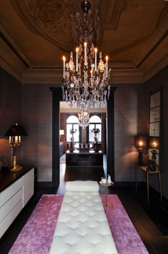 dark entryway with pink carpet and white tufted bench