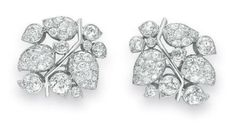 A PAIR OF DIAMOND AND PLATINUM CLIPS, BY SUZANNE BELPERRON. Each designed as a foliate cluster, the polished platinum vine extending bezel-set old European-cut diamond flower buds and old European and single-cut diamond leaves, mounted in platinum and 18k white gold, circa 1935, with French assay marks, (with 18k white gold detachable ear clips of later addition.) With maker's mark for Suzanne Belperron