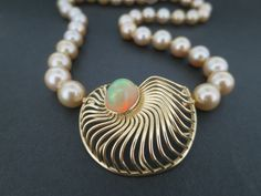 """An 18k yellow gold """"Modullyn"""" ammonite clasp bezel set with an 8.04ct val cabochon orange natural Etheopian opal."""