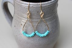 A pair of drop earrings that feature dyed turquoise beads. The turquoise beads…