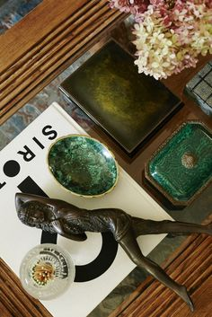 Emerald green coffee table decor pieces, a coffee table book, and flowers.