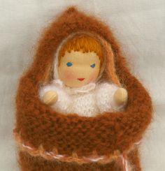 Die Wiegenpüppchen haben Kopf und Hände aus Stoff. Ihr Körperchen ist aus zarter (Mohair)- Wolle gestrickt und mit Schafwolle gestopft.Zudem tragen die Wiegenpüppchen eine gestrickte Mütze. Haare,...