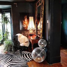 Black wicker chair w/ sheepskin. Disco ball plants