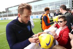 BURTON-UPON-TRENT, ENGLAND - MARCH 19: Harry Kane of England signs autographs for fan during an England training session during an England Media Access day at St Georges Park on March 19, 2019 in Burton-upon-Trent, England. (Photo by Matthew Lewis/Getty Images)
