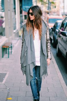 Sea salt spray-textured hair back tucked into blanket vest loose ripped jeans gold and black aviators