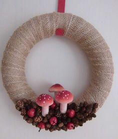 Zelfgemaakte krans voor de herfst. De krans met jute omwikkelt en voorzien van decoratie ( decoratie appeltjes, paddenstoelen en dennenappels )