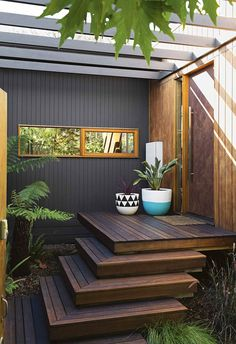 Rich natural timber tones are contrasted with dark painted timber cladding and vibrant potted plants to create a warm welcome. Cascading decks create an easy staircase to the door.
