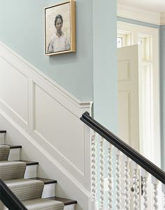 Wainscoting and woodwork painted in a light white set off the blue-gray walls of this entry hall and stairway wall, designed by Madeline Stuart.   - HouseBeautiful.com