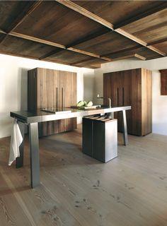 bulthaup - b2 keuken - keukenwerkbank, bestaande uit twee zijwaartse spanklauwen, een roestvrijstalen module voor de spoelunit en de kookzone. Met daarnaast nog een notenhouten module, aangevuld met een keukenwerkkast en een keukenapparatenkast in notenhout en een afvalelement met een notenhouten afdekking