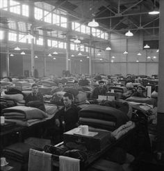 "Italian Prisoners of War stand beside their beds in the large warehouse-like dormitory at the N.144 workers camp near London. According to the original caption ""the camp is sub-divided into 5 large dormitories in which are found 2-tiered bunks. These dormitories have central heating. Every bunk is further provided with a mattress and 4 blankets in the winter (in the summer they have only 3)""."