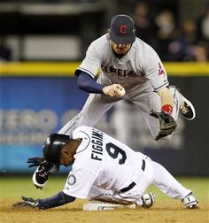 Seattle Mariners' Chone Figgins (9) slides in hard to second base to force Cleveland Indians shortstop to jump rather than throw to first on a grounder from Dustin Ackley in the sixth inning of a baseball game Wednesday, April 18, 2012, in Seattle. Figgins was out and Ackley safe at first.