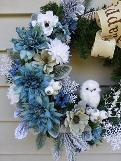 Make your home look more inviting with this gorgeous holiday wreath. This is a combination of three blue dahlias, white mum, white and green anemone, Christmas picks and snowflakes Tied with a Happy Holiday ribbon to create a holiday atmosphere. A little white owl is standing in the