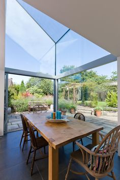 Double height dining room with Structurally glazed frameless corner window / roof with sliding pocket door