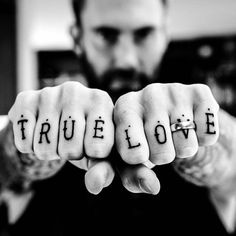 """Matching knuckle tattoo on Adam Levine. Each finger has been tattooed with a capital letter which spells out """"True Love"""". Tattoo Artist: Bryan Randolph"""