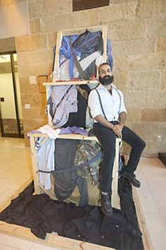 """Artist Michael Anthony Garcia with his installation """"Exo XO"""" at The People's Gallery in Austin City Hall (photo by Jana Birchum for Austin Chronicle)"""