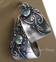 Those beautiful ornate with floral motives wide hoops were made from Fine silver and blue chalcedony. Has been oxidized to give it a more antique and