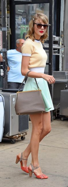 Taylor Swift street style:  Taylor embraced her inner pinup-girl in this retro-inspired look that included a ringer tee, flared skirt and structured bag.