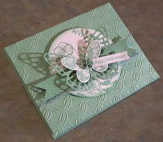 This pretty tone on tone card was made using one of the newest Stampin Up In Colors, Mint Macaron and coordinating products. The card measures 5 1/2 x 4 1/4 and was made using card stocks, the Butterfly Basics & Teeny Tiny Wishes stamp sets, butterfly dies, lace & blossom accents from Stampin Up. The embossed panel has been adhered to a piece of fun foam for added dimension, as well as the hand stamped circle panel. I have also added a hand stamped banner, which is layered onto the piece…