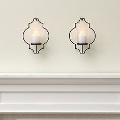 Shop Set of 2 Rosaline Metal Wall Candle Holders.  Classical wallpaper medallions streamline as contemporary outlines in bronze steel, projecting out from the wall to support a single glass-enclosed candle holder.