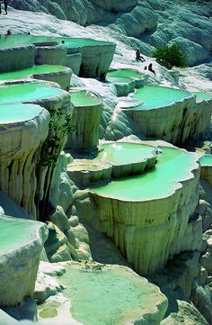 Pamukkale ('cotton castle' in Turkish) is a natural site in Denizli Province, Turkey, containing hot springs and travertines, terraces of carbonate minerals left by the flowing water. People have bathed in its pools for thousands of years.