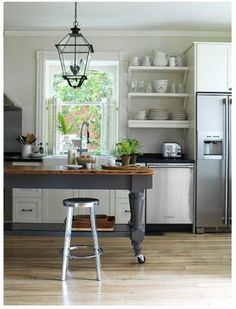 Add casters to a farmhouse table for a counter height workspace and dining space in the kitchen.