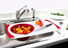 """Promising review: """"I have very limited counter space, and if there's any dirty dishes in the sink or on the counter, cooking is a struggle. BUT, this cutting board goes over the sink, so I can wash my veggies and fruits, cut them up, and toss them into the strainer. The only rub is that the strainer isn't well attached to the cutting board so when you try to push down to open up the strainer, it detaches from the board. Other than that I love it, and will be replacing any and everything I…"""