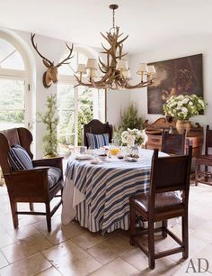 The breakfast room's tableware is by Ralph Lauren Home, as are the fabrics used for the tablecloth and the cushions on the 19th-century English armchairs; the painting is 17th-century Dutch.