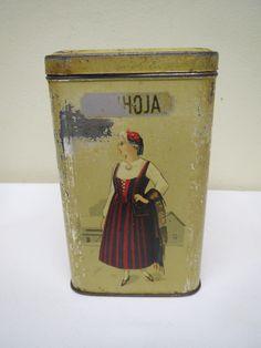 Vanha peltipurkki, joka sivulla  eri kansallispukua kantava nainen, patinaa. 18 euroa.