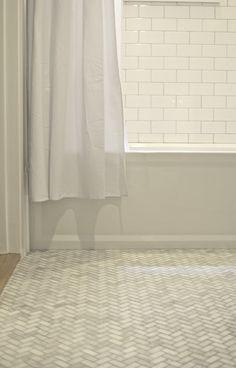 White subway tile walls and marble herringbone floors