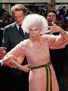 The Duchess of Alba (throwing a gang sign?) about to topple over while man in background laughs.