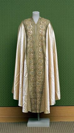 Cape 1930s Cream silk satin hooded cape, cut in the shape of a semi-circle, with applied embroidered floral border, silk tassel on hood.