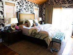 The contrast of vaulted pine ceilings and richly textured wallpaper perfectly compliments a bed piled high with pillows and comforters.