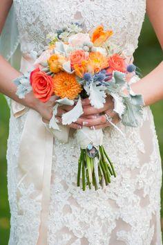 Bride's Pretty Bouquet Which Includes: Blue Eryngium Thistles, Pastel Pink Roses, Orange Roses, Coral Roses, White Astrantia, Orange Parrot Tulips, Orange Dahlias, Silver Brunia, Dusty Miller