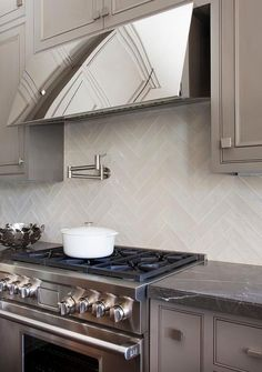 Beautifully gray kitchen is equipped with a stainless steel hood mounted beneath and between gray cabinets to white herringbone backsplash tiles above a stainless steel oven range flanked by gray inset cabinets topped with a black marble countertop.