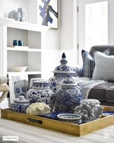 3 façons de styler votre table à café ou votre taverne Style your coffee table with a clustered grouping of blue and white ginger jars and accessories. Use the same idea for any monochromatic display. Blue And White Living Room, Blue And White Vase, Blue Rooms, White Rooms, Table Cafe, Decorating Coffee Tables, Coffee Table Displays, Decor For Coffee Table, Coffee Table Styling