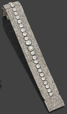 A magnificent Art Deco diamond and platinum bracelet, by CHAUMET, circa 1920. The articulated bracelet pavé set with brilliant-cut diamonds, centring a line of 23 brilliant-cut diamonds of graduating sizes, mounted in platinum. Signed Joseph Chaumet. #JosephChaumet #ArtDeco #bracelet